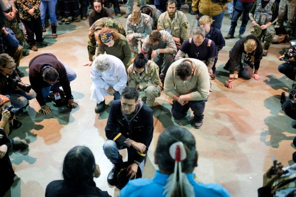 Gen. Wesley Clark Jr. and other veterans kneel in front of Leonard Crow Dog during a forgiveness ceremony at the Four Prairie Knights Casino & Resort on the Standing Rock Sioux Reservation on Monday, Dec. 5, 2016.